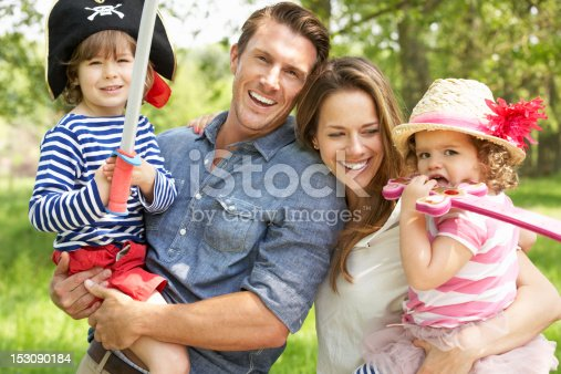 Parents Playing Exciting Adventure Game With Children In Summer Field Smiling