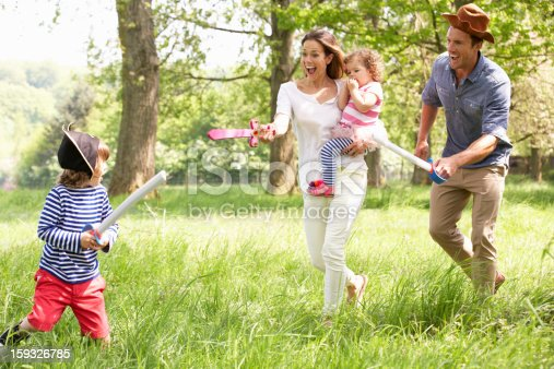 Parents Playing Exciting Adventure Game With Children In Summer Field Laughing And Having Fun