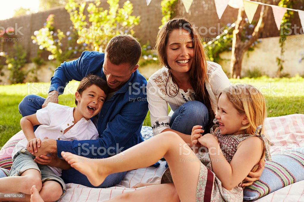 Parents Playing Game With Children On Blanket In Garden royalty-free stock photo