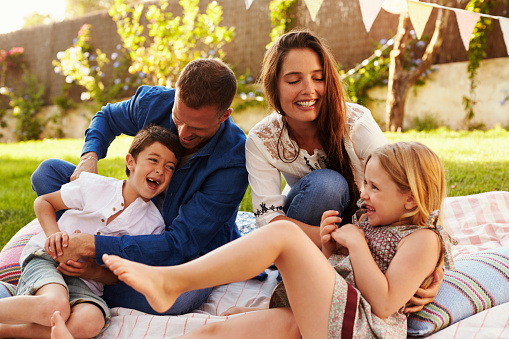 Parents Playing Game With Children On Blanket In Garden Stock Photo - Download Image Now