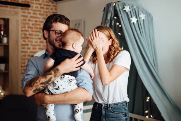 Parents playing hide and seek with their baby boy Parents playing hide and seek with their baby boy hide and seek stock pictures, royalty-free photos & images