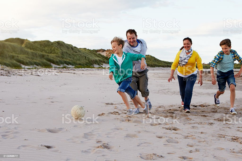 Parents Playing Soccer With Children On Beach stock photo