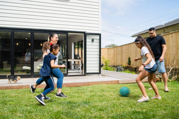 Parents playing soccer with kids in backyard. stock photo