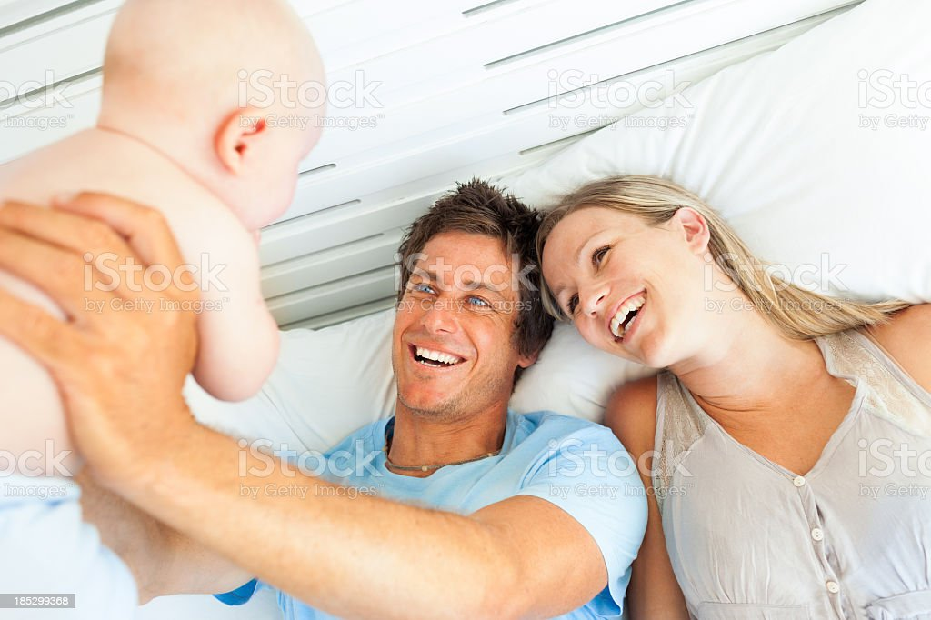 Parents Playing With Baby In Bed stock photo