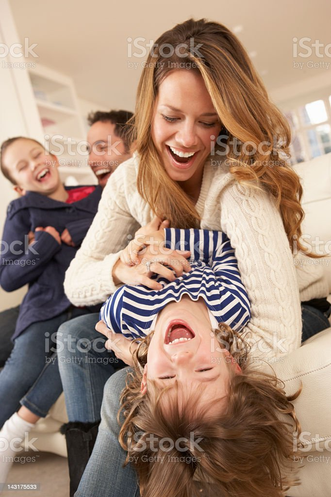 Parents playing with children at home stock photo