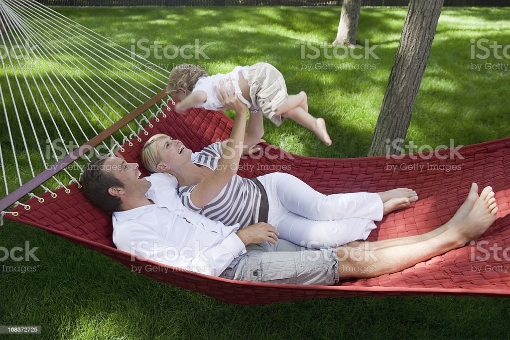 Parents Playing With Their Baby Boy In Hammock royalty-free stock photo