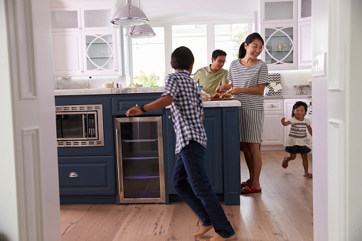 Parents Prepare Food As Children Play In Kitchen