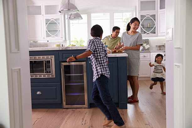 parents prepare food as children play in kitchen - busy stock photos and pictures