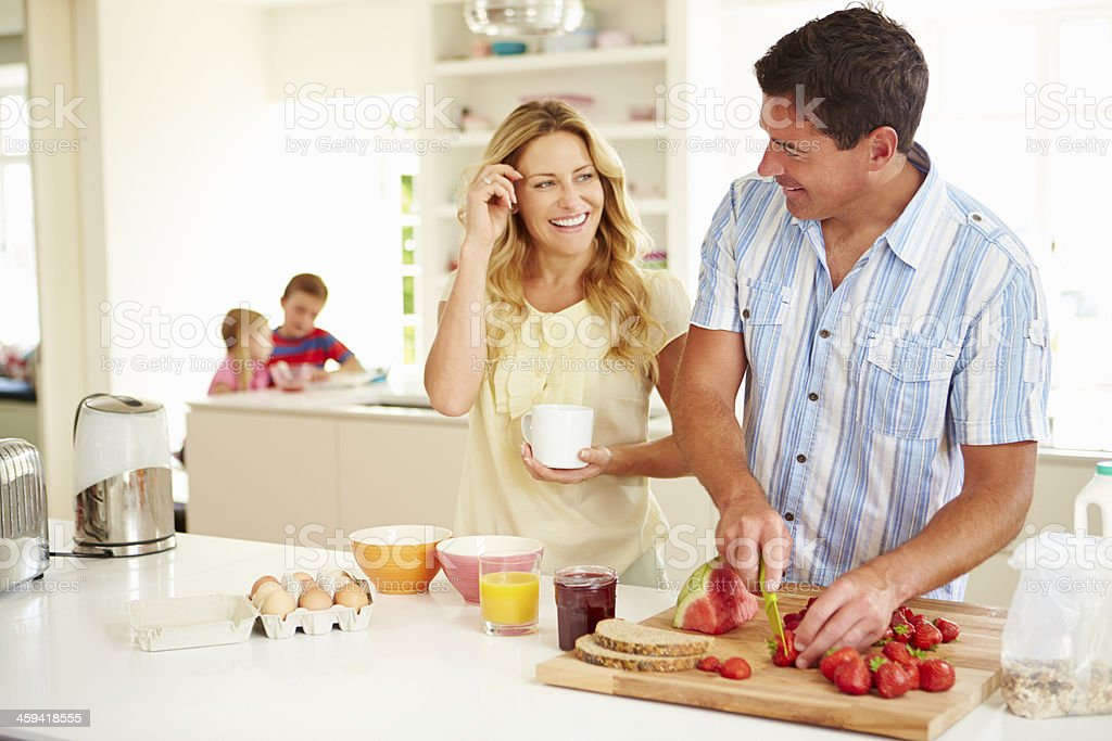 Parents Preparing Family Breakfast In Kitchen stock photo
