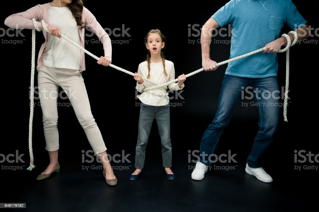 parents pulling over shocked daughter with rope stock photo