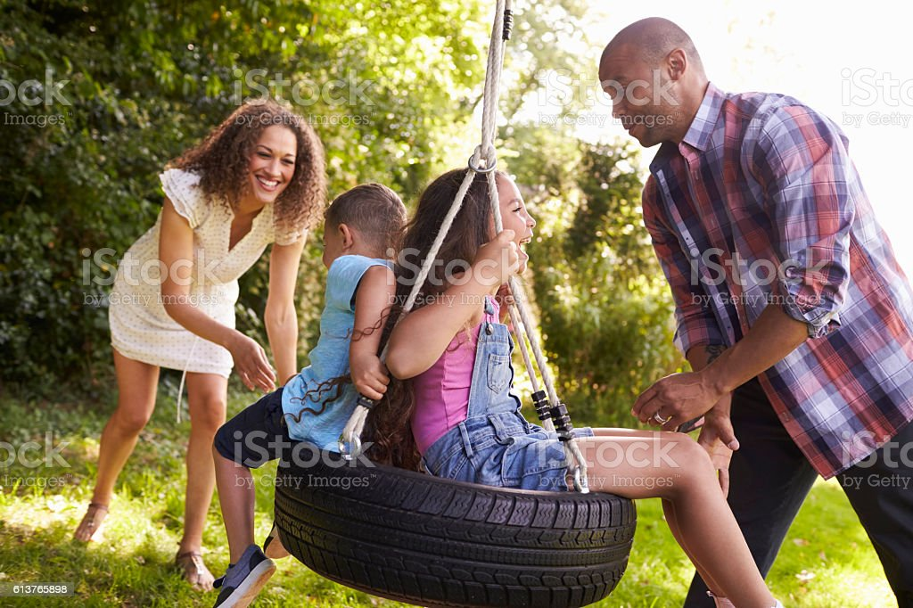 Parents Pushing Children On Tire Swing In Garden stock photo