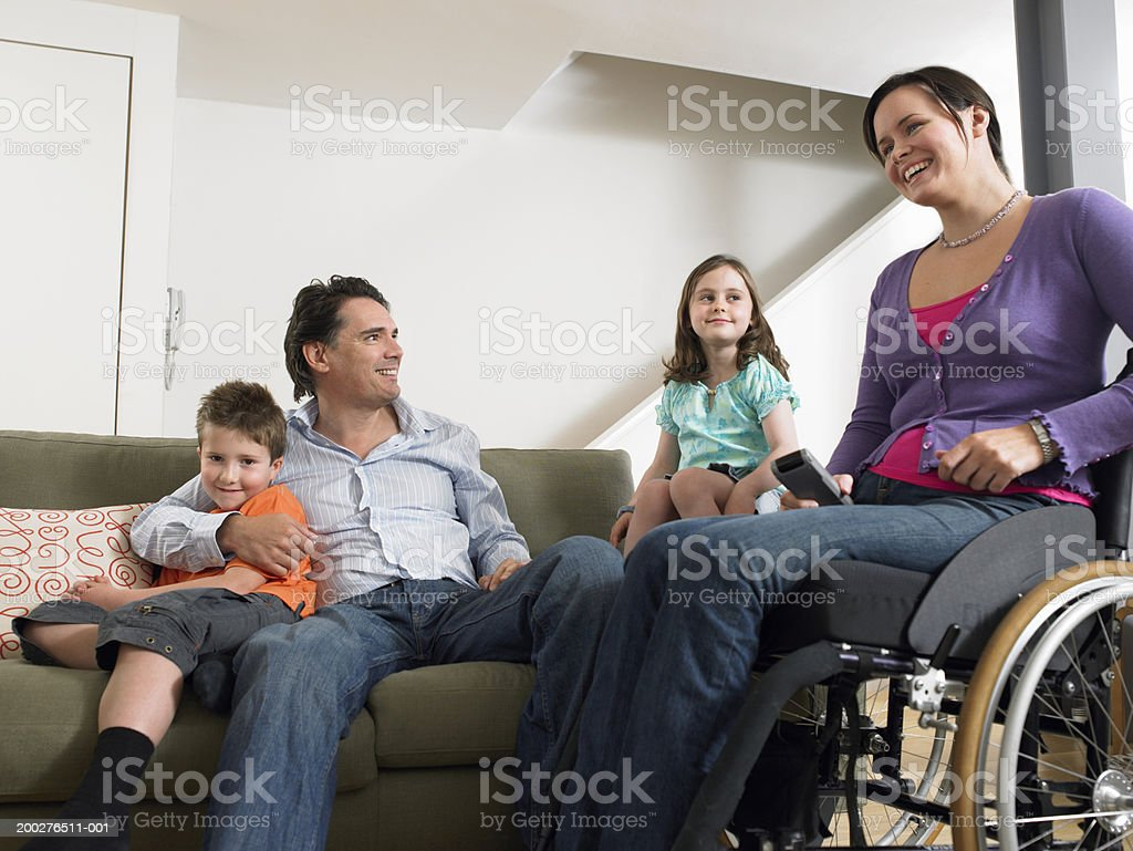 Parents relaxing in living room with son and daughter (7-9) woman in wheelchair, smiling stock photo