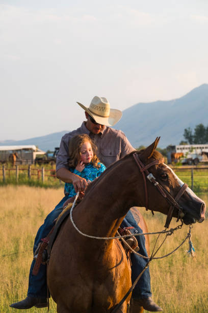Parents Riding Horses With Their Daughters stock photo
