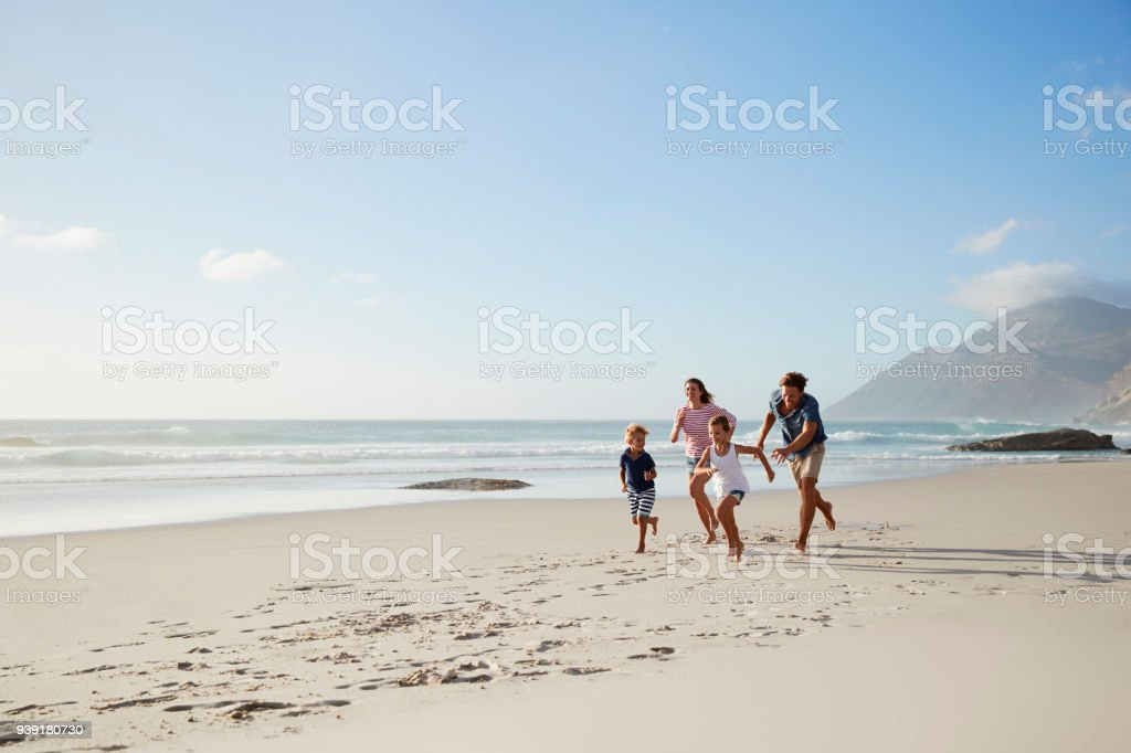 Parents Running Along Beach With Children On Summer Vacation stock photo