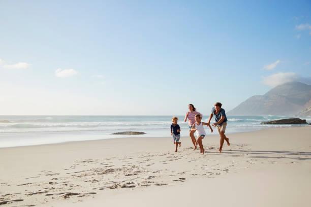 Parents Running Along Beach With Children On Summer Vacation - fotografia de stock