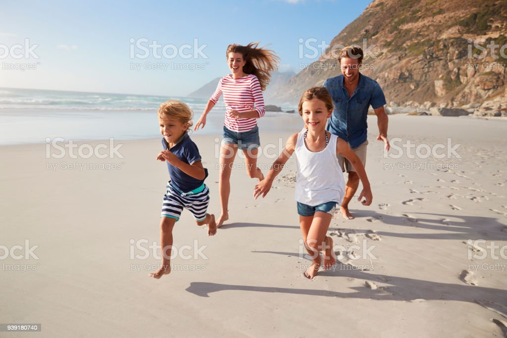 Parents Running Along Beach With Children On Summer Vacation royalty-free stock photo