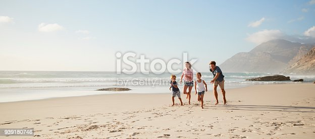 istock Parents Running Along Beach With Children On Summer Vacation 939180746