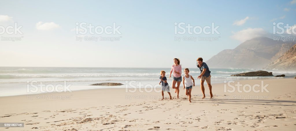 Parents Running Along Beach With Children On Summer Vacation - foto stock