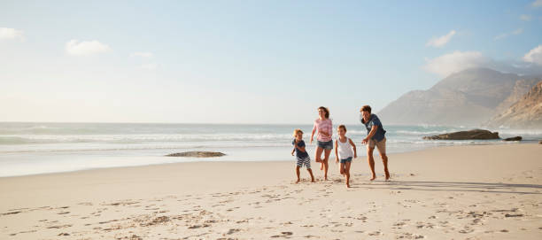 parents running along beach with children on summer vacation - family vacation stock photos and pictures