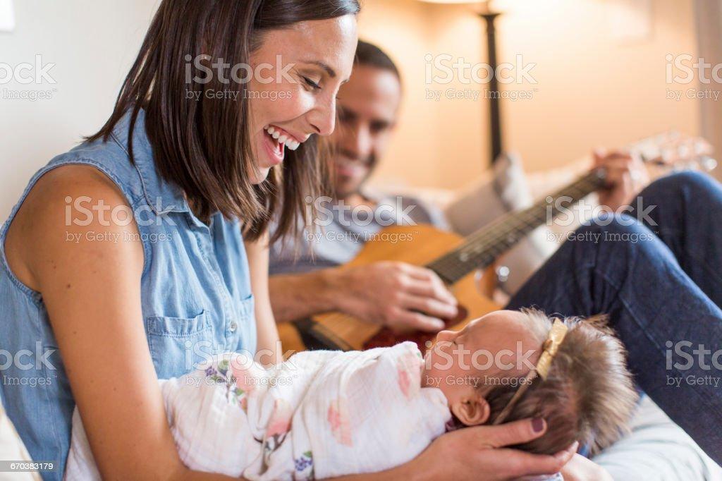 Parents serenade baby girl, lovingly stock photo