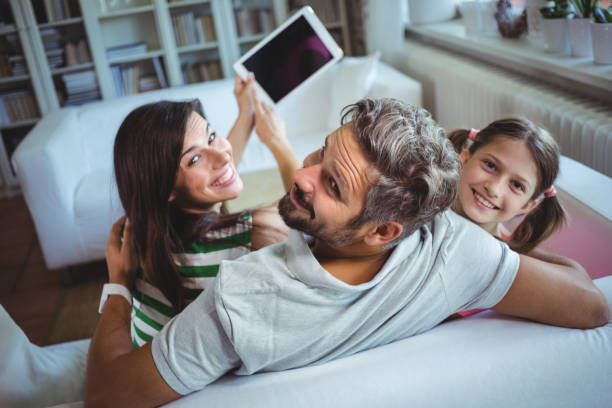 Parents sitting on sofa with daughter and clicking a selfie on digital tablet stock photo