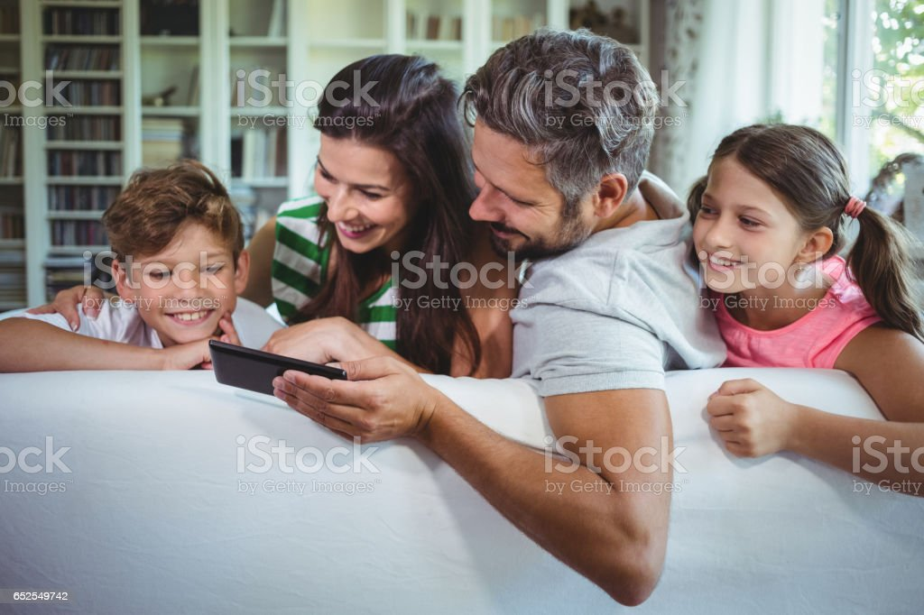Parents sitting on sofa with their children and using mobile phone in living room stock photo
