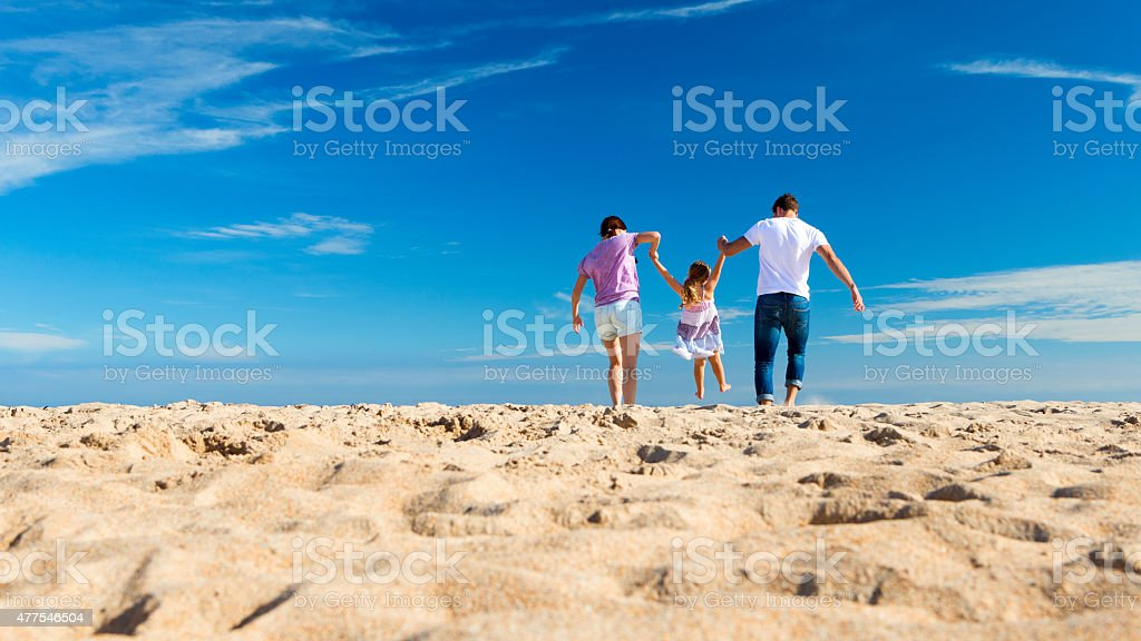 Parents Swing Child on Beach stock photo