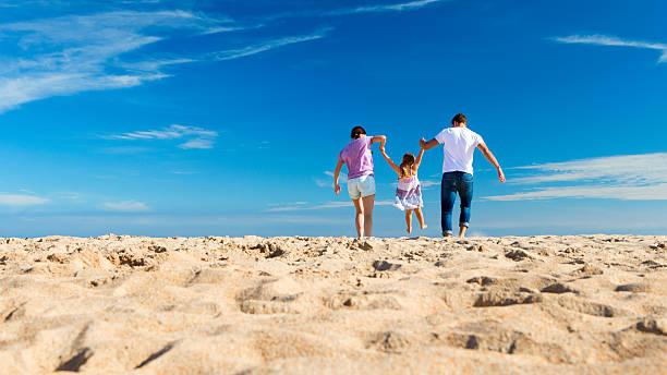 Eltern spielen Kind am Strand – Foto