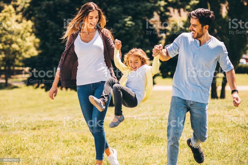 Ouders die hun dochter swingende in de lucht foto