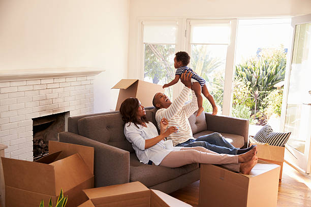 parents take a break on sofa with son on moving day - house hunting stock photos and pictures