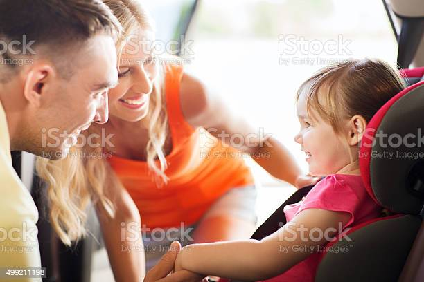 Padres Hablando De Bebé Niña En Un Asiento De Coche Foto de stock y más banco de imágenes de 2015