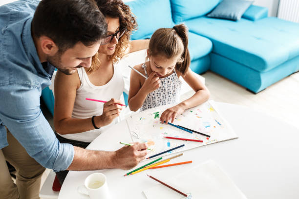 Parents teach they young daughter to draw. stock photo