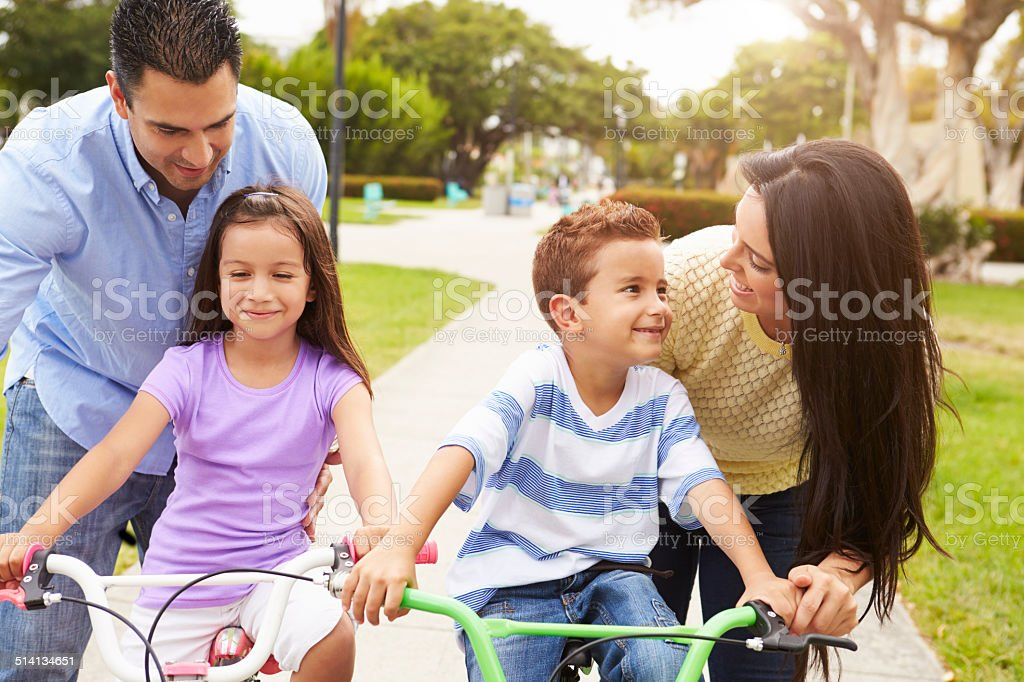 Parents Teaching Children To Ride Bikes In Park stock photo