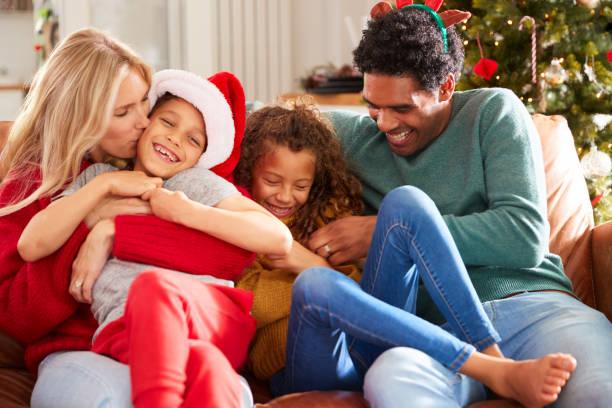 ouders kietelen kinderen als familie zitten op de bank vieren kerst samen - christmas family stockfoto's en -beelden