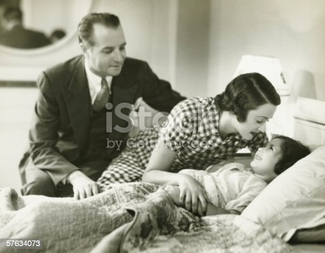 57520540 istock photo Parents tucking daughter (6-7) into bed, (B&W) 57634073