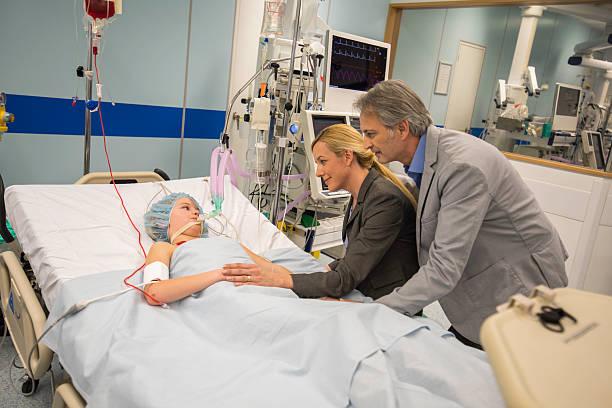 parents visiting young son in hospital - ventilator bed stockfoto's en -beelden