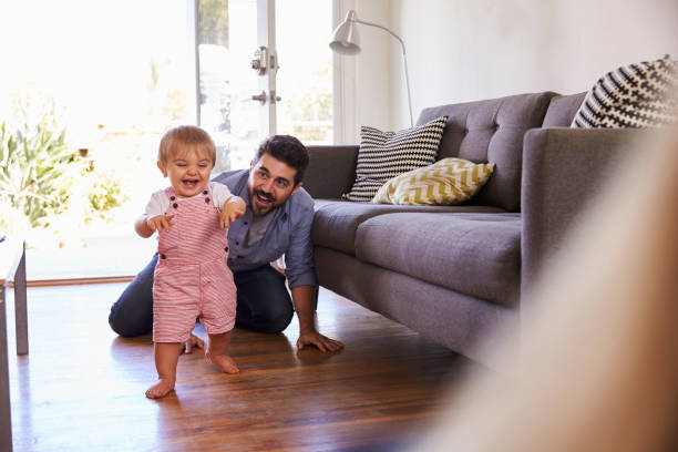 parents watching baby daughter take first steps at home - first step stock photos and pictures