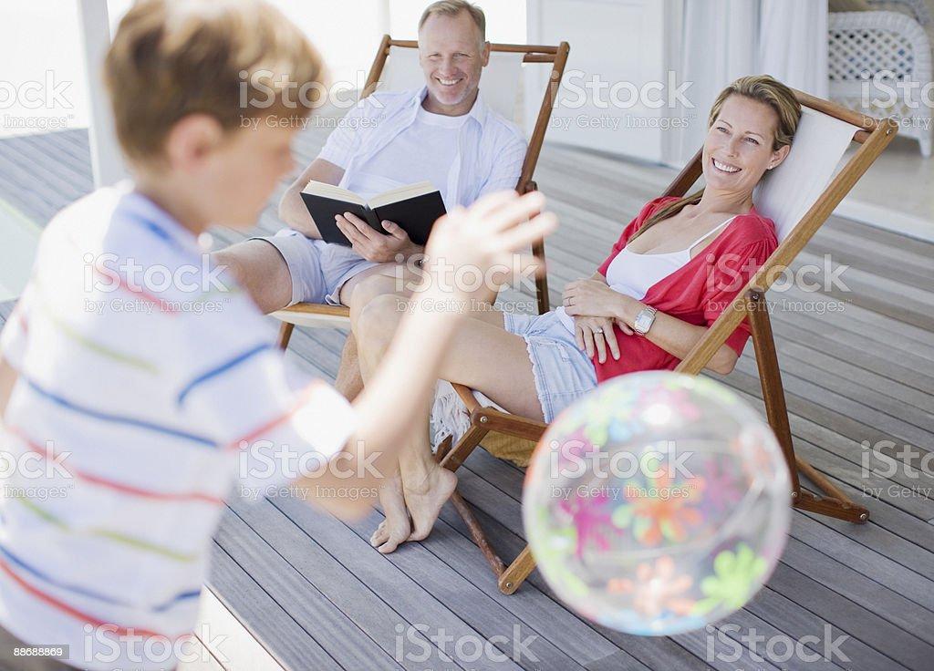 Parents en regardant son fils jouent avec le ballon sur la terrasse photo libre de droits