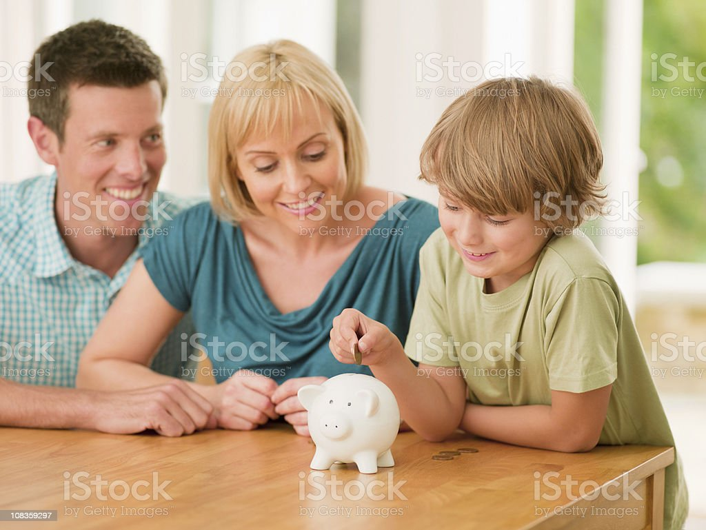 Parents watching son putting coin into piggy bank stock photo