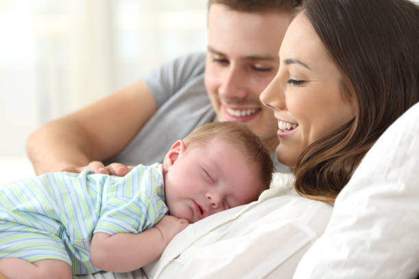 parents watching their baby sleeping - new baby stock photos and pictures