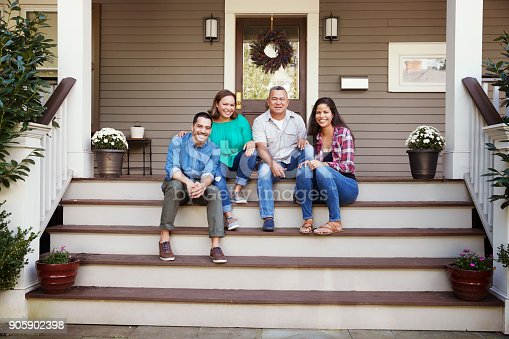 istock Parents With Adult Offspring Sitting On Steps in Front Of House 905902398