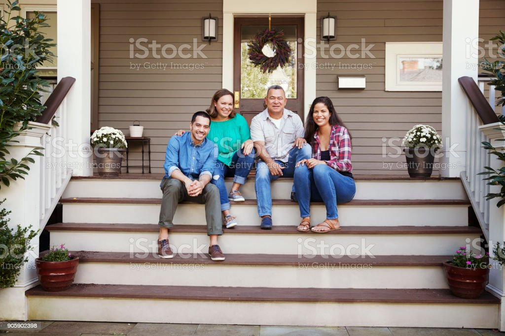 Parents With Adult Offspring Sitting On Steps in Front Of House stock photo