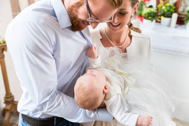 Parents with baby at christening in church stock photo