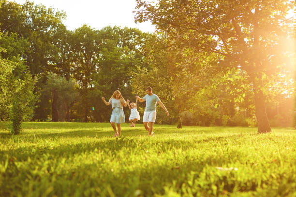 Parents with baby stands on grass in the park stock photo