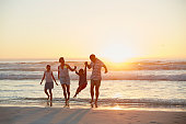 Full length of parents with children enjoying vacation on beach during sunset