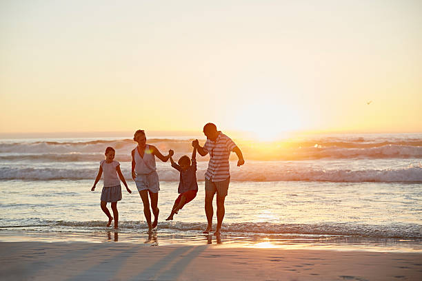 Parents with children enjoying vacation on beach stock photo