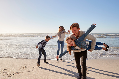 istock Parents With Children Having Fun On Winter Beach Together 935359846