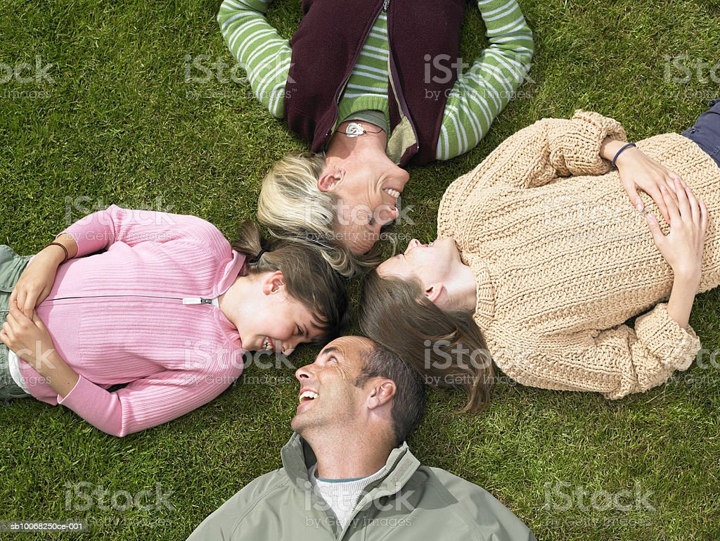 Parents with children (8-13) lying on grass, elevated view royalty-free stock photo