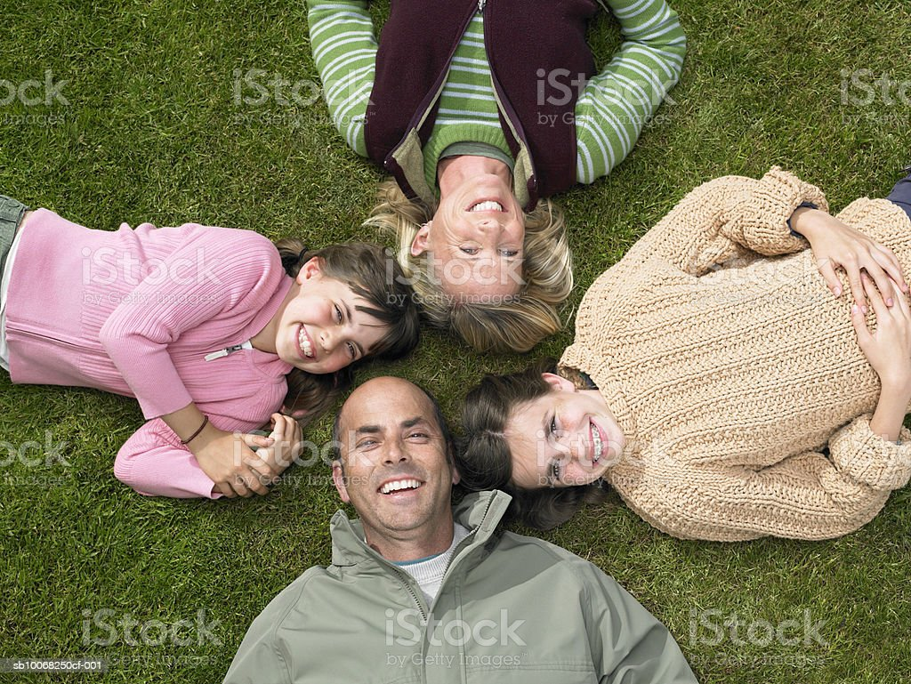 Parents with children (8-13) lying on grass, elevated view, portrait 免版稅 stock photo