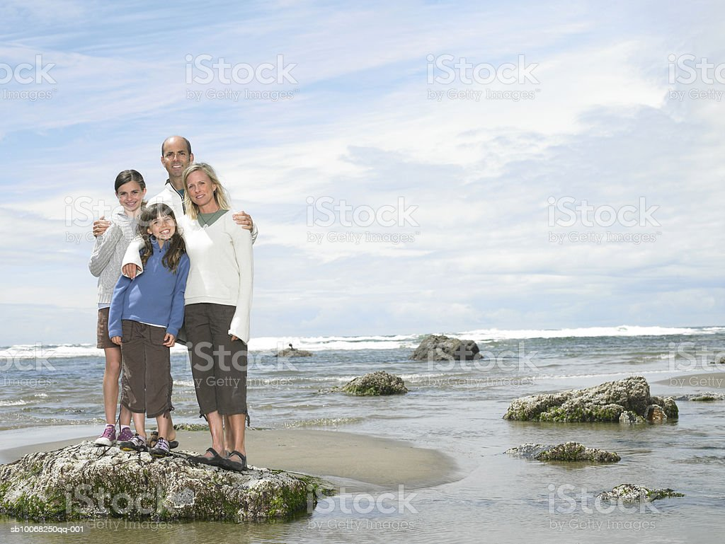 Parents with children (8-13) on beach, smiling, portrait royalty-free stock photo